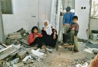 Rodina v Rafáhu sedící v ruinách svého domu